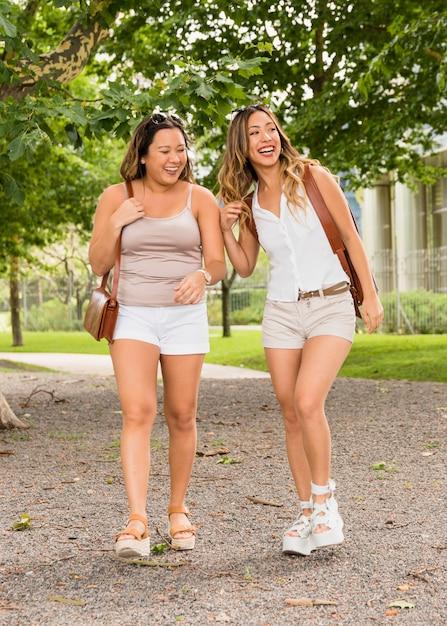 Retrato de duas turista feminina em shorts curtindo a viagem Foto gratuita