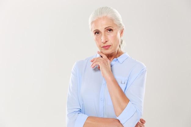 Retrato de encantadora senhora séria, camisa azul, tocando o queixo Foto gratuita
