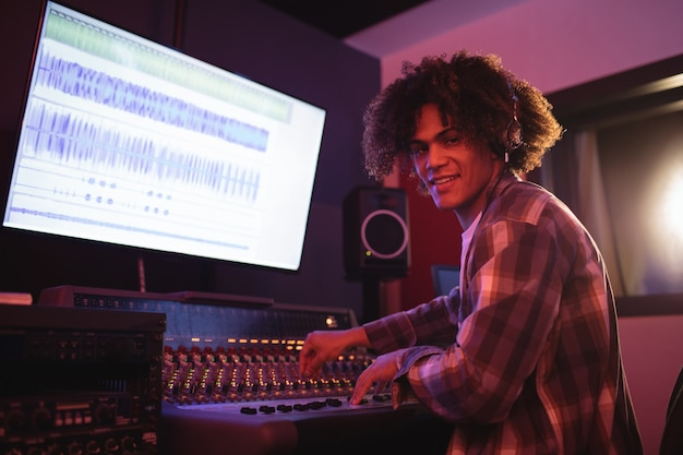 Retrato de engenheiro de áudio usando mixer de som Foto gratuita