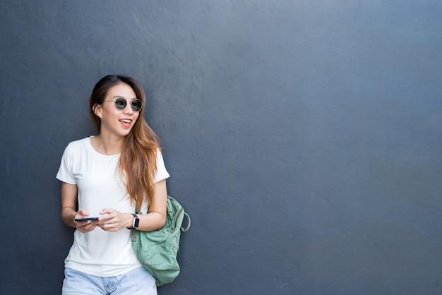 Retrato de estilo de vida ao ar livre de muito sexy jovem garota asiática no estilo de viagem e óculos na parede cinza Foto gratuita