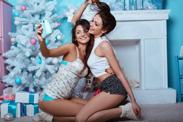 Retrato de estilo de vida interior de duas garotas loucas hipster de melhores amigos Foto Premium