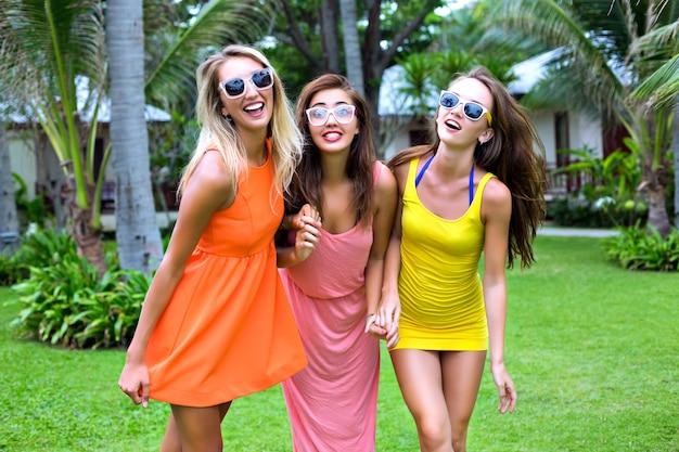 Retrato de estilo de vida tropical de verão de três melhores amigas felizes se divertindo ao ar livre, usando vestidos sexy coloridos, estilo de praia de festa de férias, jardim exótico, óculos de sol com roupas da moda, relaxamento, alegria Foto gratuita