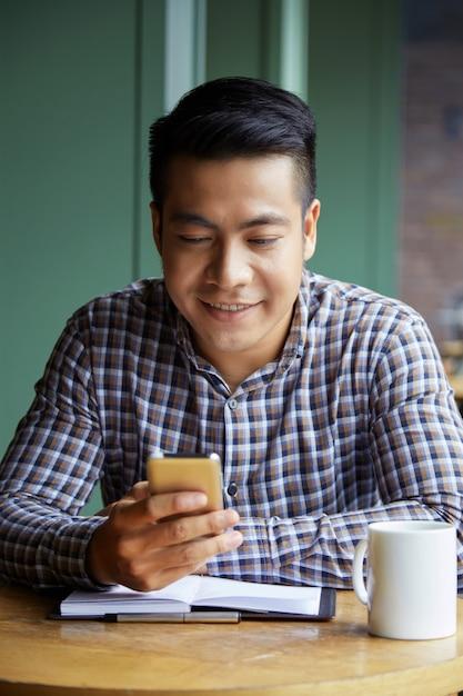 Retrato de estudante asiática, navegar na net em smartphone no coffeeshop Foto gratuita