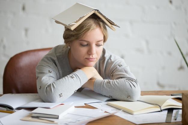 Retrato de estudante com livro aberto na cabeça Foto gratuita