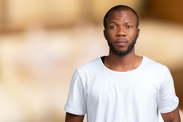 Retrato de estudante masculino africano stong e bonito, olhando para a câmera sorrindo Foto Premium