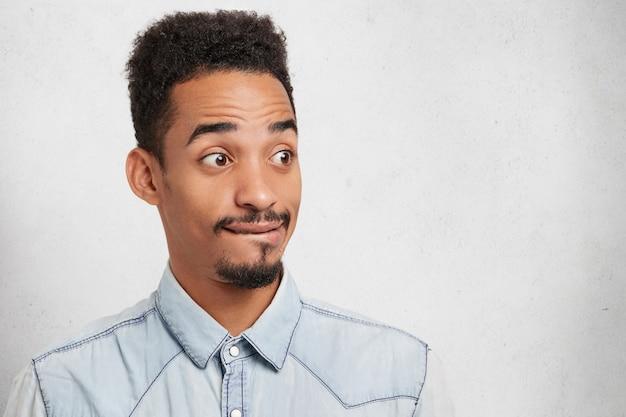 Retrato de estúdio de um homem atraente com aparência específica, parece com olhos esbugalhados, tem expressão pensativa, Foto gratuita
