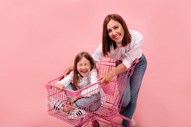 Retrato de estúdio de uma mulher europeia atraente com sua filha sentada em uma cesta de compras rosa com os olhos fechados Foto gratuita