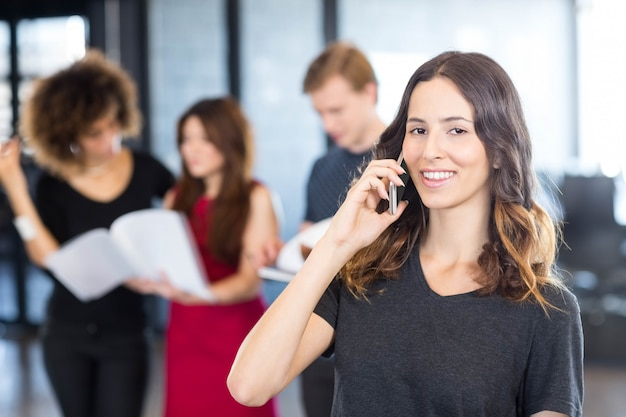 Retrato, de, executiva, falar telefone móvel, enquanto, dela, colegas, estar, dela, em, escritório Foto Premium