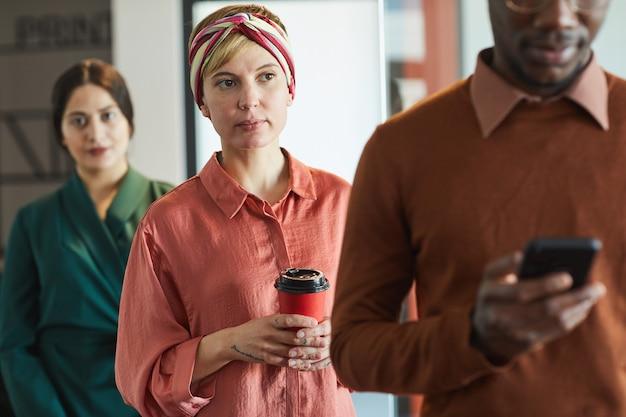 Retrato de executivos em pé na fila do escritório, foco na jovem mulher moderna segurando a xícara de café Foto Premium