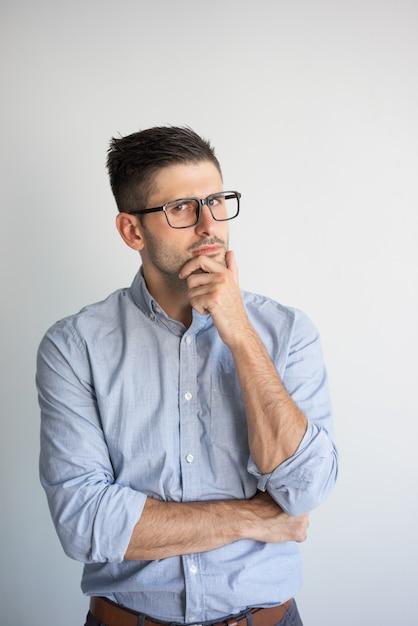 Retrato de eyeglasses desgastando do homem de negócios novo pensativo. Foto gratuita
