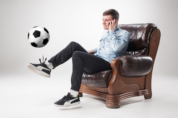 Retrato de fã com bola, segurando o controle remoto da tv em branco Foto gratuita