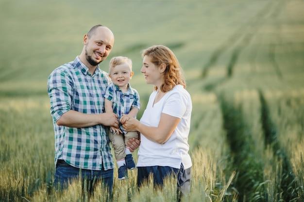 Retrato de família adorável entre o campo de vegetação Foto gratuita