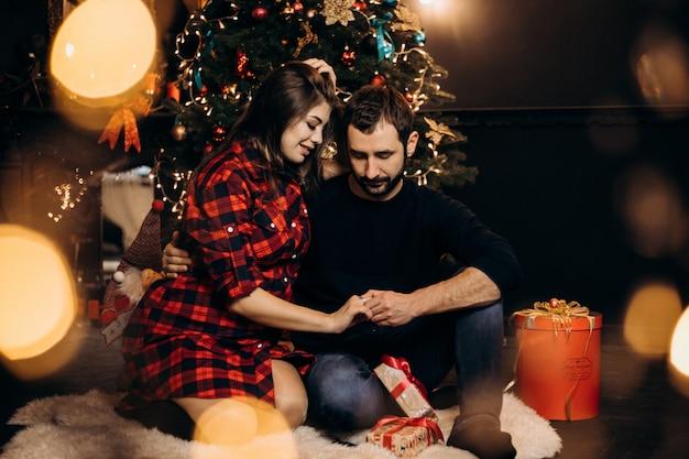 Retrato de família. casal charmoso de mulher grávida em camisa e homem bonito posar em um aconchegante Foto gratuita