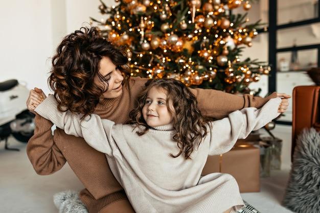 Retrato de família da jovem mãe feliz e da linda filha se divertindo e comemorando a festa de natal com presentes Foto gratuita