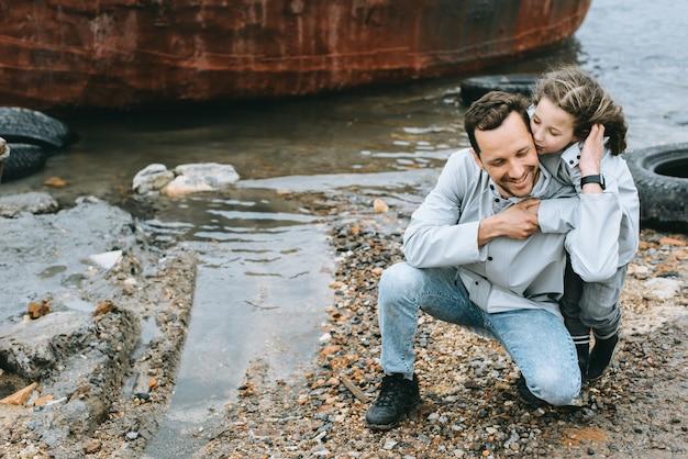 Retrato de família do pai e dauther na capa de chuva perto do mar Foto Premium