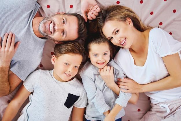 Retrato de família feliz deitada na cama Foto gratuita