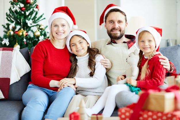 Retrato de família feliz sentado no sofá com chapéus de papai noel Foto gratuita