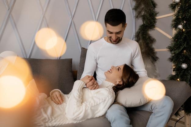 Retrato de família. homem mulher, relaxe, ligado, cinzento macio, mau, em, um, sala, com, árvore natal Foto gratuita