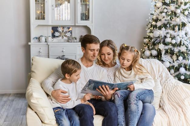 Retrato de família lendo livro na noite de natal Foto Premium