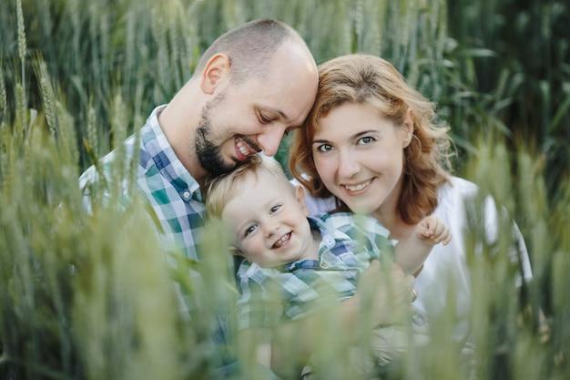 Retrato de família linda entre o campo de trigo Foto gratuita