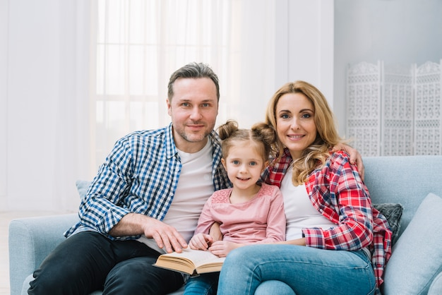 Retrato, de, família, livro leitura, junto, sentar sofá Foto gratuita
