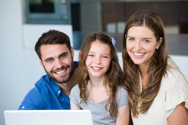 Retrato de família sorridente com laptop Foto Premium