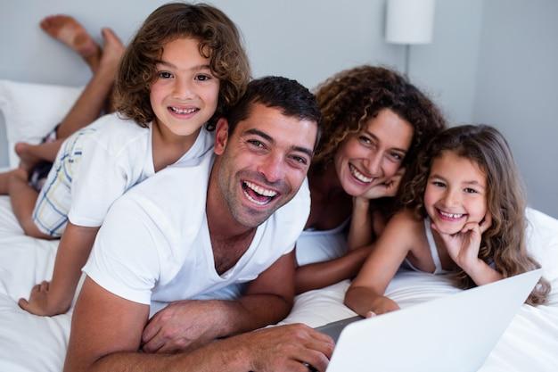Retrato de família usando laptop juntos na cama Foto Premium
