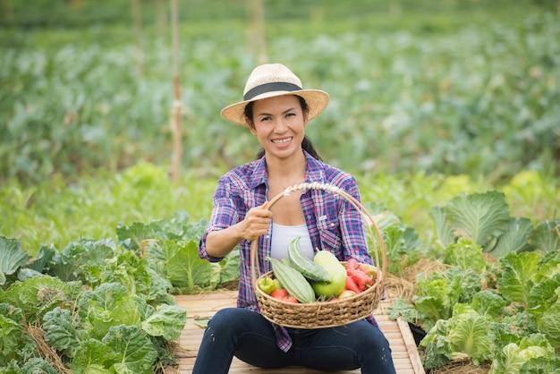 Retrato, de, feliz, agricultor feminino, segurando, um, cesta, de, legumes, em, a, fazenda Foto gratuita