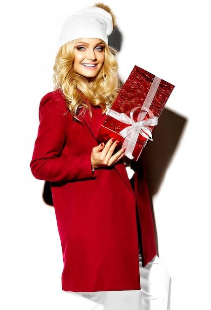 Retrato de feliz doce sorridente mulher loira bonita segurando nas mãos dela grande caixa de presente de natal em roupas de inverno casual vermelho hipster Foto gratuita