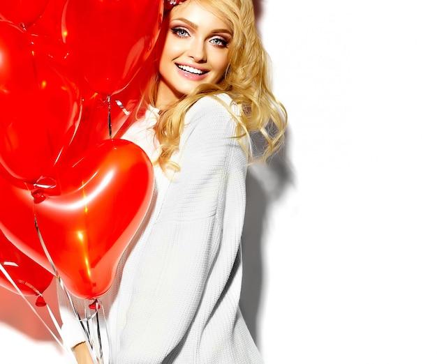Retrato de feliz doce sorridente mulher loira linda segurando nas mãos dela grande caixa de presente de natal e balões de coração em roupas de inverno casual hipster vermelho, em camisola quente branca Foto gratuita