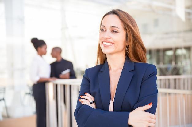Retrato, de, feliz, executiva, e, dela, empregados, em, fundo Foto gratuita
