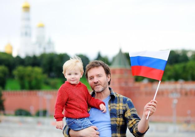 Retrato, de, feliz, família, com, bandeira russa, com, kremlin moscow Foto Premium