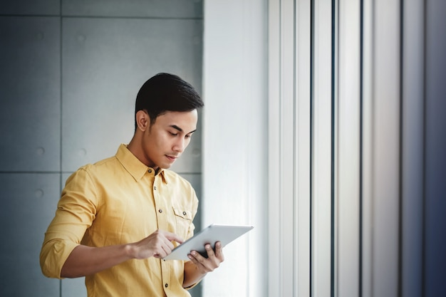 Retrato, de, feliz, homem negócios fica, por, a, janela, em, escritório Foto Premium