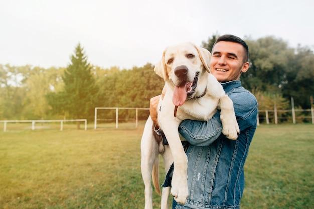 Retrato, de, feliz, homem, segurando, seu, amigo, cão, labrador, em, pôr do sol, parque Foto gratuita