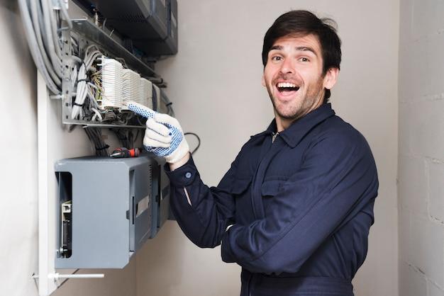 Retrato, de, feliz, macho, eletricista, apontar, tábua circuito Foto gratuita