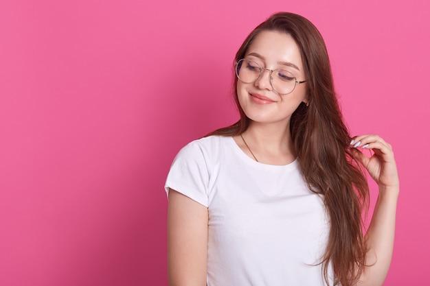 Retrato de feliz menina de cabelos castanho bonito jovem sorrindo e olhando de lado, toca o cabelo, posando isolado na rosa Foto gratuita
