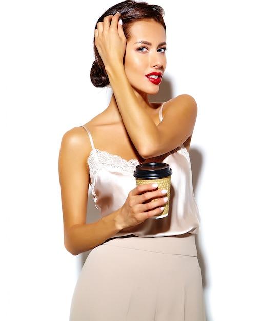Retrato de feliz mulher morena sexy bonita feliz com os lábios vermelhos em calças largas clássicas segurando a xícara de café de plástico no fundo branco Foto gratuita