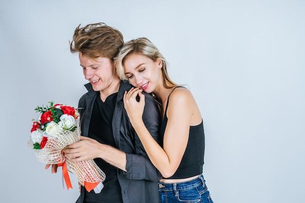 Retrato, de, feliz, par jovem, amor, junto, com, flor Foto gratuita