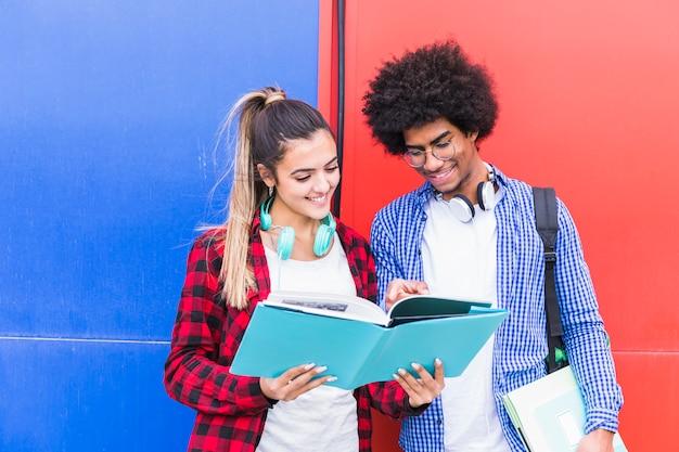 Retrato, de, feliz, par jovem, estudar, ficar, junto, contra, vermelho azul Foto gratuita