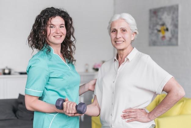 Retrato, de, femininas, fisioterapeuta, e, mulher sênior, paciente, exercitar Foto gratuita