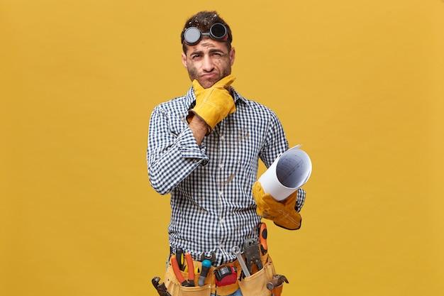 Retrato de fettler masculino vestindo roupa protetora, segurando a planta com uma expressão pensativa enquanto pensava sobre suas ações durante o trabalho. reparador com kit de instrumentos isolado na parede Foto gratuita