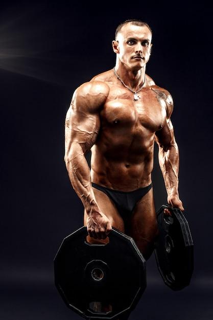 Retrato de fisiculturista com halteres nos braços Foto Premium