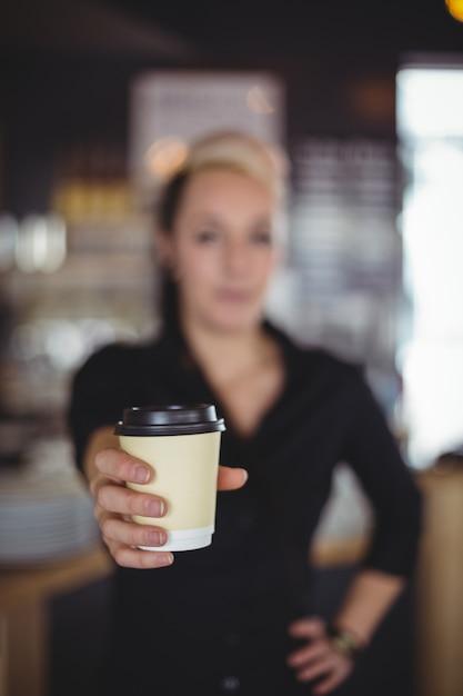 Retrato, de, garçonete, ficar, com, descartável, xícara café Foto gratuita