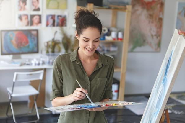 Retrato de giro artista feminina trabalhando na oficina, pintando com pincel e aquarelas, em pé perto de cavalete, sendo feliz em dedicar-se ao seu hobby. jovem talentoso pintor desenho Foto gratuita