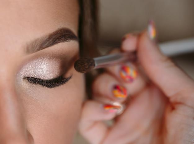 Retrato de glamour linda mulher com cabelos cacheados escuros, maquiagem artista acabamento compõem a noiva na manhã do casamento Foto Premium