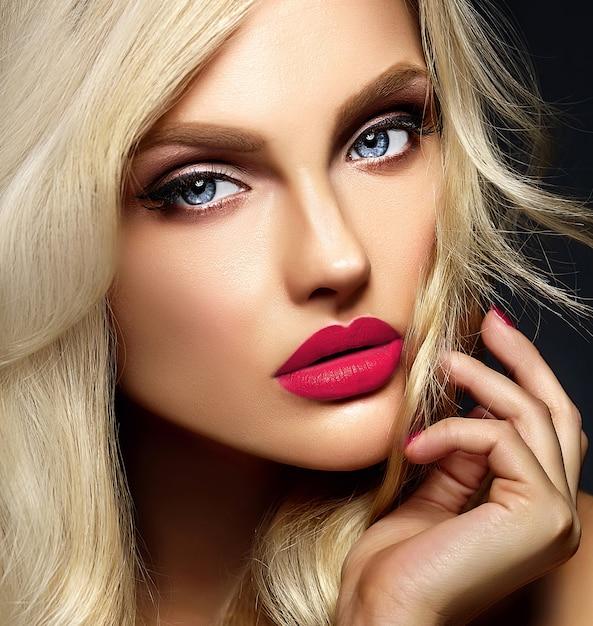 Retrato de glamour sensual da senhora modelo linda mulher loira com maquiagem brilhante e lábios cor de rosa, com cabelos cacheados saudáveis em fundo preto Foto gratuita