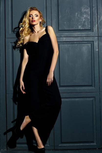 Retrato de glamour sensual da senhora modelo linda mulher loira com maquiagem fresca em traje preto clássico em pé perto da parede Foto gratuita