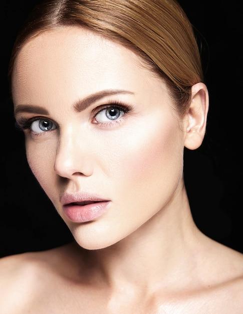 Retrato de glamour sensual do modelo de mulher bonita sem maquiagem e pele limpa e saudável em preto Foto gratuita