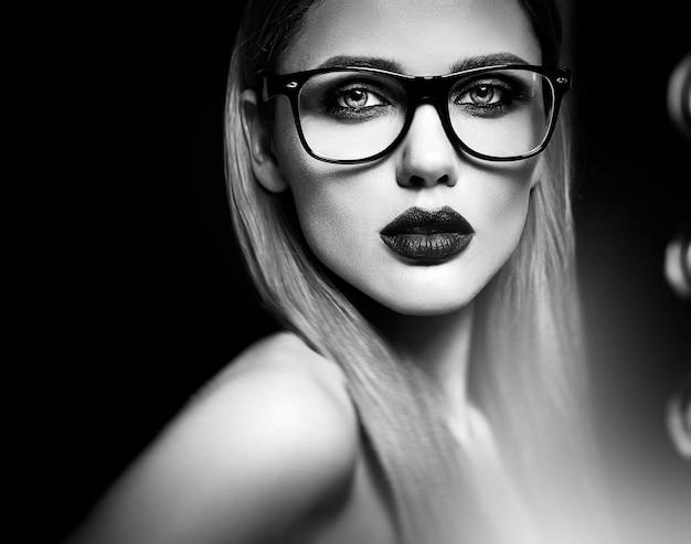 Retrato de glamour sensual do modelo de mulher loira bonita com maquiagem diária fresca com lábios roxos cor e pele limpa e saudável em copos. preto e branco Foto gratuita