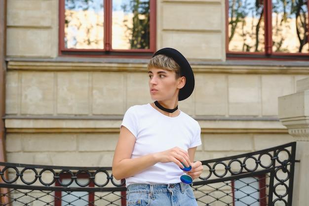 Retrato de hipster feminino com maquiagem natural e cabelo curto, aproveitando o tempo de lazer ao ar livre Foto gratuita